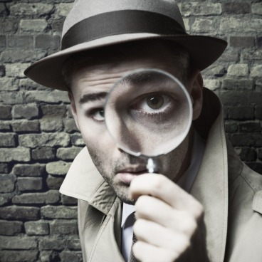 vintage-detective-looking-through-a-magnifier-picture-id501362758