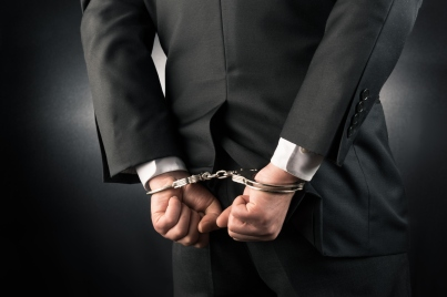 Businessman is arrested and handcuffed